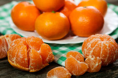 Tasty peeled and unpeeled clementines. Tasty sweet peeled and unpeeled clementines Royalty Free Stock Photos