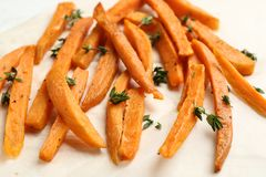 Tasty sweet potato fries on parchment. Closeup royalty free stock image