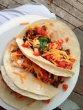 3 Tasty tacos. With cheddar cheese tomatoes chopped steak and cilantro in flour tortillas Stock Photo