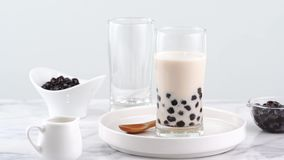 Tasty tapioca pearl bubble milk tea in glass, popular drink in taiwan on bright marble table and white tray, homemade concept. 4K. Zoom in shot video stock footage
