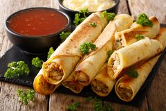 Tasty taquitos with chicken and two sauces close-up. horizontal. Tasty taquitos with chicken and two sauces close-up on the table. horizontal Stock Image