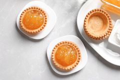 Tasty tartlets with jam on light background. Top view Stock Photo