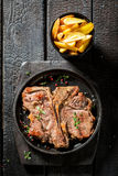 Tasty tbone steak and chips with herbs and salt Stock Photo
