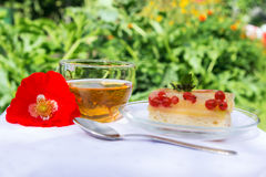 Tasty tea cake and poppy flower on white cloth. Cup of tea and tasty piece of cake on white cloth Royalty Free Stock Image