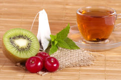 Tasty tea in cup with fruits Stock Image