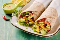 Tasty Tex-Mex vegetarian avocado tortilla wraps. With nachos, chili, coriander and salad trimmings served with a side dish of guacamole Royalty Free Stock Photo
