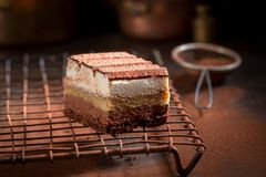 Tasty tiramisu cake with cocoa, mascarpone and biscuits. On dark table royalty free stock images