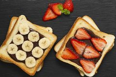 Tasty toast bread with banana, strawberry and chocolate on a black plate. royalty free stock photos
