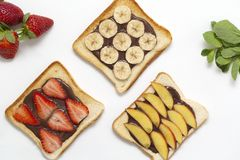 Tasty toast bread with chocolate paste, banana, strawberry and peach on white background. stock photography
