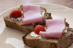 Tasty toasts with butter, ham and cherry tomatoes Royalty Free Stock Photos
