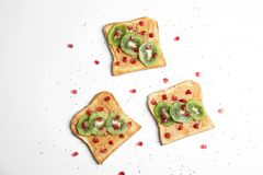 Tasty toasts with kiwi, peanut butter, pomegranate and chia seeds on white background. Top view stock photo
