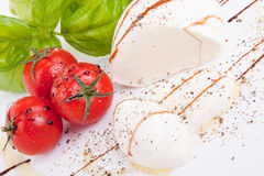 Tasty tomatoe mozzarella salad with basil on white Stock Photos