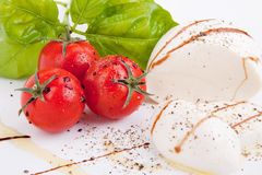 Tasty tomatoe mozzarella salad with basil on white Stock Photo