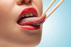 The tasty tongue. The photo of girl lower face with eating sticks hoding tongue Stock Image