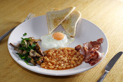 Tasty and traditional breakfast. Tasty english breakfast with eggs,bacon,bean,mushrooms and bacon Stock Photography