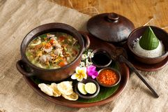Tasty traditional dishes call soto betawi in brown bowl. Traditional dishes call soto betawi in brown bowl with rice, chilly sauce and lemon with flowers royalty free stock photos