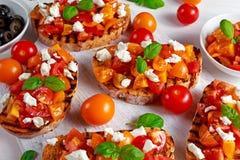 Tasty Traditional Tomato bruschetta with feta cheese topping, fresh basil. Stock Photo