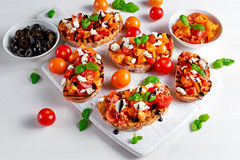 Tasty Traditional Tomato bruschetta with feta cheese topping, fresh basil and balsamic vinegar Royalty Free Stock Image