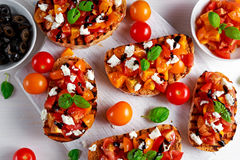 Tasty Traditional Tomato bruschetta with feta cheese topping, fresh basil and balsamic vinegar Royalty Free Stock Photography