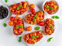 Tasty Traditional Tomato bruschetta with fresh basil on white board Stock Photos