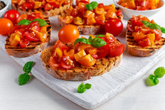 Tasty Traditional Tomato bruschetta with fresh basil on white board Royalty Free Stock Photography