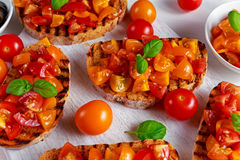 Tasty Traditional Tomato bruschetta with fresh basil on white board Stock Images