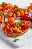Tasty Traditional Tomato bruschetta with fresh basil on white board Stock Photo