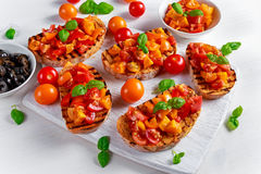 Tasty Traditional Tomato bruschetta with fresh basil on white board Stock Photography