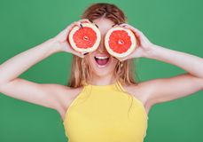 Tasty tropical fruits! Attractive sexual woman with beautiful makeup holding fresh juicy grapefruit or orange near face on isolate stock photo