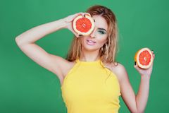 Tasty tropical fruits! Attractive sexual woman with beautiful makeup holding fresh juicy grapefruit or orange near face on isolate stock photography