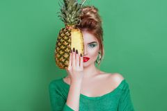 Tasty tropical fruits! Attractive sexual woman with beautiful makeup holding fresh juicy pineapple and looking at cam on isolated stock photography