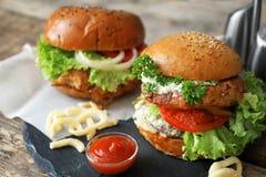 Tasty turkey burgers. On slate plate Royalty Free Stock Images