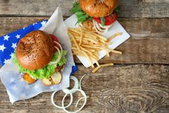 Tasty turkey burgers. On wooden background Royalty Free Stock Photography