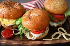 Tasty turkey burgers. On wooden board Royalty Free Stock Photos