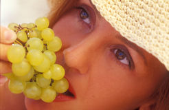 It is tasty and useful. A girl eats green grape Royalty Free Stock Photos