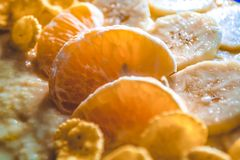 Tasty and useful breakfast from fruit and flakes. Segments of tangerines and pieces of bananas. Vitamins. stock image
