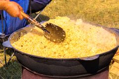 Tasty Uzbek pilaf in a cauldron on fire in the open air at street food festival. Spring sunny day royalty free stock image
