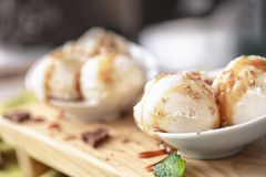 Tasty vanilla ice-cream balls with caramel topping. In bowl on board Royalty Free Stock Photo