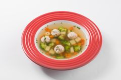 Tasty vegetable soup with broccoli and chicken balls. In red plate isolated on a white background Stock Images