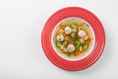 Tasty vegetable soup with broccoli and chicken balls. In red plate isolated on a white background. top view Stock Image