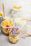 Tasty vegetables salads in jars with corn and  sprouts on light rustic kitchen table, close up. Stock Photography