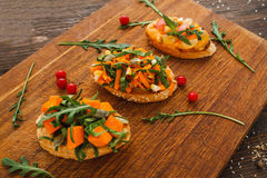 Tasty vegetarian canapes on wooden board. Tree portions of bruschetta with pumpkin and herbs. Recipe, healthy food, creative snack, seasonal snack concept Royalty Free Stock Image