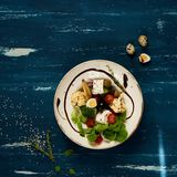 Tasty vegetarian salad. Made of quail eggs, lettuce, Feta cheese, broccoli, cauliflower, olives and baby corn on plate standing on blue old wooden table Stock Photo