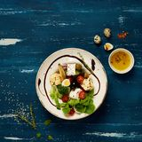 Tasty vegetarian salad. Made of quail eggs, lettuce, Feta cheese, broccoli, cauliflower, olives and baby corn on plate standing on blue old wooden table Stock Photos