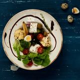 Tasty vegetarian salad. Made of quail eggs, lettuce, Feta cheese, broccoli, cauliflower, olives and baby corn on plate standing on blue old wooden table Stock Images