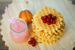 Tasty waffles on wooden board with fresh berries. Belgian waffles with fresh berries on cutting board on background of rustic. grapefruit juice. pink cocktail Royalty Free Stock Photography