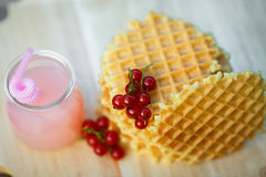 Tasty waffles on wooden board with fresh berries. Belgian waffles with fresh berries on cutting board on background of rustic. grapefruit juice. pink cocktail Royalty Free Stock Photo