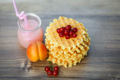 Tasty waffles on wooden board with fresh berries. Belgian waffles with fresh berries on cutting board on background of rustic. grapefruit juice. pink cocktail Stock Photo