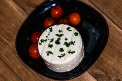 Tasty white cheese with spices and cherry tomatoes on cutting board