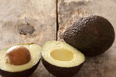 Tasty whole and halved ripe avocado pears Stock Image